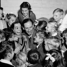 Peter Brough with his Ventriloquist Dummy, Archie Andrews, surrounded by delighted children at Holmer School